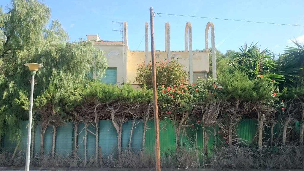 Current status of one of the 3 façades overlooking the street and appearance of one of the sections of the 111 linear-metres-perimeter of the exterior fence up to the beginning of the fence construction works in September of the present year.